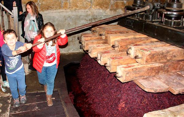Niños participando en el prensado de la uva